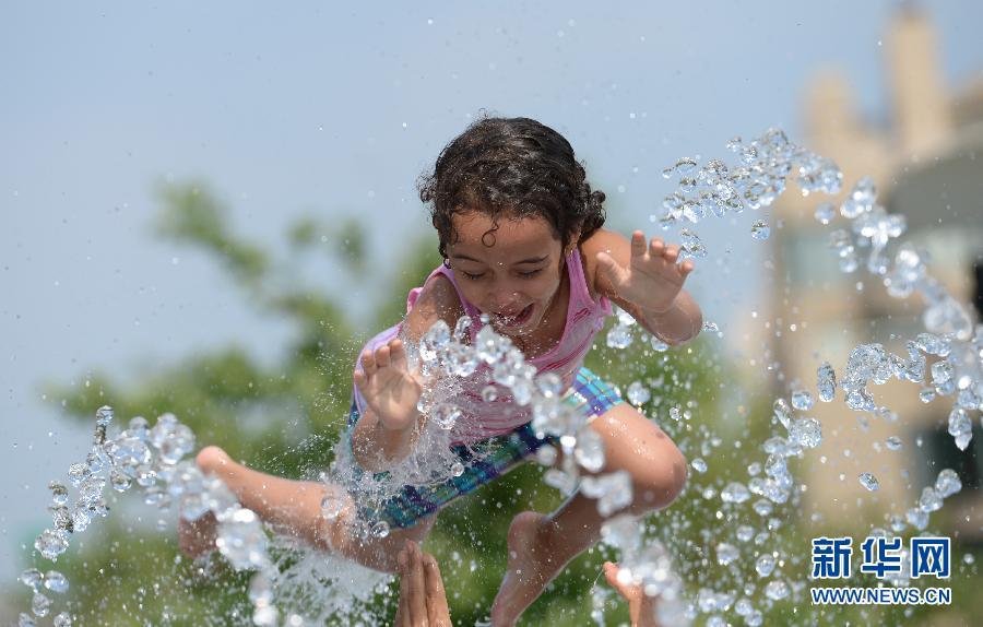 6月18日,一名儿童在美国首都华盛顿的一处喷泉中玩水祛暑.