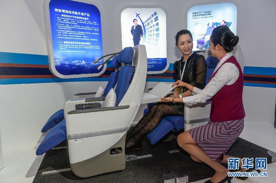 11月11日,南航的一名工作人员(右)向参观者介绍南方航空公司推出的经济舱升级产品。南方航空公司在第十届中国航展上推出经济舱升级产品,为乘客提供更舒适的座椅和宽敞的空间,并升级地面和机上服务。 新华社记者刘大伟摄