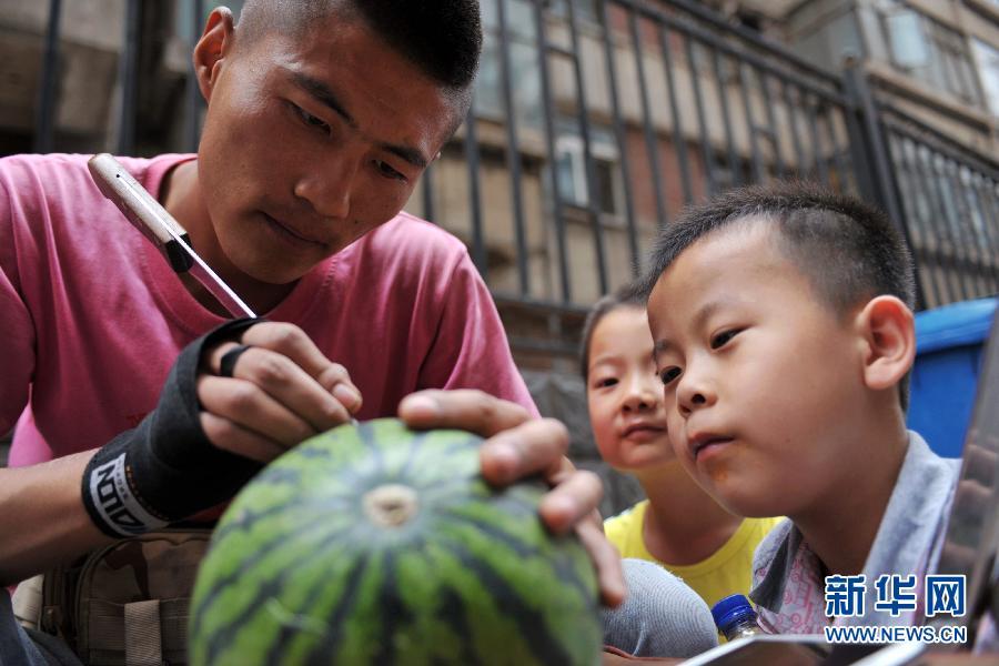 艺术 沈栋彬/7月4日,两个孩子在观看沈栋彬雕刻西瓜。