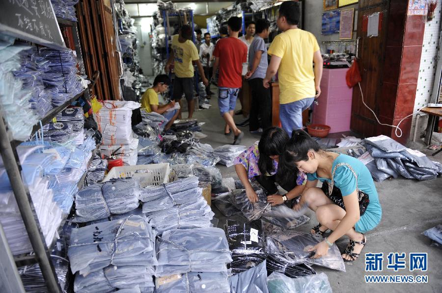 淘宝/在军埔村里一家经营服装批发的淘宝店,村里各家店铺的工作人员...