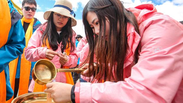 志愿者将来自长江源头的水注入容器,永久珍藏